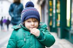 Porträt des kleinen Kleinkindjungen, der durch die Stadt auf Kälte geht Lizenzfreies Stockfoto