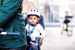 Porträt des kleinen Kleinkindmädchens mit Sicherheitssturzhelm auf dem Kopf, der im Fahrradsitz und ihr Vater oder Mutter mit sit stockfotos