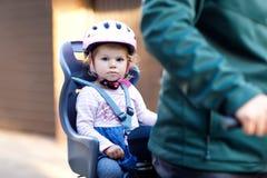 Porträt des kleinen Kleinkindmädchens mit Sicherheitssturzhelm auf dem Kopf, der im Fahrradsitz und ihr Vater oder Mutter mit sit lizenzfreies stockfoto