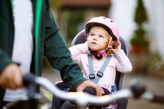 Porträt des kleinen Kleinkindmädchens mit Sicherheitssturzhelm auf dem Kopf, der im Fahrradsitz und ihr Vater oder Mutter mit sit stockfotografie