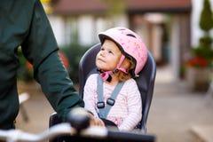 Porträt des kleinen Kleinkindmädchens mit Sicherheitssturzhelm auf dem Kopf, der im Fahrradsitz und ihr Vater oder Mutter mit sit lizenzfreie stockfotografie