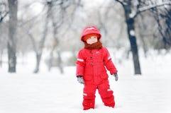 Porträt des kleinen lustigen Jungen in der roten Winterkleidung, die Spaß mit Schnee während der Schneefälle hat Lizenzfreies Stockfoto