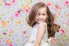 Porträt des kleinen Mädchens auf Blumenhintergrund stockbild