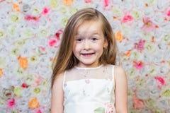 Porträt des kleinen Mädchens auf Blumenhintergrund stockfoto