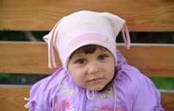 Porträt des kleinen Mädchens, das auf einer Bank sitzt Lizenzfreie Stockfotos