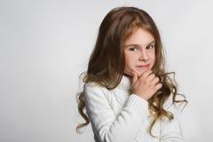 Porträt des kleinen Mädchens denkend, über einem Grau Stockfotografie