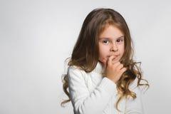 Porträt des kleinen Mädchens denkend, über einem Grau Lizenzfreie Stockfotografie