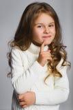 Porträt des kleinen Mädchens denkend, über einem Grau Lizenzfreie Stockbilder