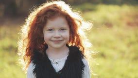 Porträt des kleinen Mädchens der netten Rothaarigen, das in einen Herbstpark geht Langsame Bewegung Bäume, die noch mit etwas gol stock footage