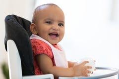Porträt des kleinen Mädchens des kleinen Afroamerikaners, das ihre Milch hält Stockfotografie