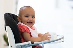 Porträt des kleinen Mädchens des kleinen Afroamerikaners, das ihre Milch hält Stockbilder