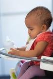 Porträt des kleinen Mädchens des kleinen Afroamerikaners, das ihre Milch hält Lizenzfreies Stockbild