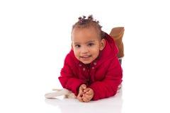 Porträt des kleinen Mädchens des kleinen Afroamerikaners, das sich auf Th hinlegt Stockbild