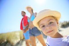Porträt des kleinen Mädchens gehend in Richtung zum Strand mit ihren Eltern Lizenzfreies Stockfoto
