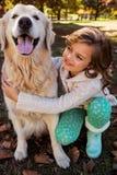 Porträt des kleinen Mädchens ihren Hund umfassend Stockfoto