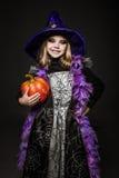 Porträt des kleinen Mädchens im Hexenkostüm mit Kürbis Halloween-Charakter Lizenzfreies Stockbild