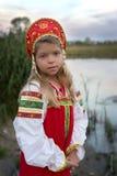 Porträt des kleinen Mädchens kleidete im russischen nationalen Kostüm auf natürlichem Hintergrund an Stockfotografie