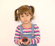 Porträt des kleinen Mädchens mit einem Spielzeug in den Händen auf einem hellen Hintergrund Lizenzfreie Stockfotografie