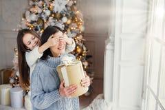 Porträt des kleinen Mädchens schließt Mutter, die ` s mustert, beglückwünscht sie mit neuem Jahr, oder Weihnachten, Stand nahe Fe stockfotografie