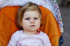 Porträt des kleinen netten Kleinkindmädchens, das im Spaziergänger oder im Pram sitzt und spazierengeht Glückliches nettes Babyki Stockfotos