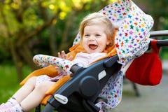 Porträt des kleinen netten Kleinkindmädchens, das im Spaziergänger oder im Pram sitzt und spazierengeht Glückliches nettes Babyki Lizenzfreie Stockfotos