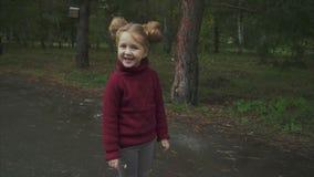 Porträt des kleinen netten lächelnden Mädchens im Herbstpark stock video footage