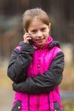 Porträt des kleinen netten Mädchens, das auf Mobile spricht Lizenzfreies Stockbild
