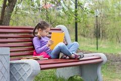 Porträt des kleinen netten Mädchens mit offenem Buch sitzt auf der Holzbank Lizenzfreie Stockfotos