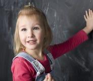 Porträt des kleinen netten Mädchens nahe Tafel Stockbilder