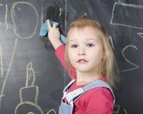 Porträt des kleinen netten Mädchens nahe Tafel Lizenzfreies Stockfoto