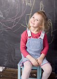 Porträt des kleinen netten Mädchens nahe Tafel Lizenzfreie Stockfotografie