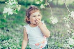 Porträt des kleinen netten ungepflegten Mädchens, das draußen Spaß unter blühenden Bäumen an einem sonnigen Sommertag lacht und h Stockfotos