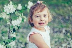 Porträt des kleinen netten ungepflegten Mädchens, das draußen Spaß unter blühenden Bäumen an einem sonnigen Sommertag lacht und h Lizenzfreies Stockbild