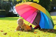 Porträt des kleinen Vorschülermädchens mit buntem Regenschirm Stockfotos
