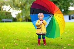 Porträt des kleinen Vorschülermädchens mit buntem Regenschirm Stockfotografie