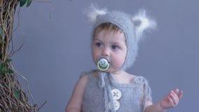 Porträt des Kleinkindes mit Friedensstifter im Mund im Kostüm mit den Ohren auf blauem Wandhintergrund stock video