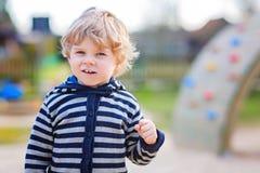 Porträt des Kleinkindjungen, der Spaß auf Spielplatz im Freien hat Lizenzfreie Stockfotos