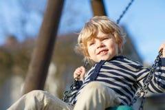 Porträt des Kleinkindjungen, der Spaß auf Spielplatz im Freien hat Stockfotografie