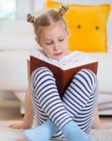 Porträt des klugen kleinen Mädchens, das mit Buch auf dem Boden sitzt Lizenzfreie Stockfotografie