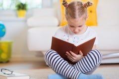 Porträt des klugen kleinen Mädchens, das mit Buch auf dem Boden sitzt Stockfotos