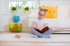 Porträt des klugen kleinen Mädchens, das mit Buch auf dem Boden sitzt Stockfotografie