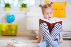 Porträt des klugen kleinen Mädchens, das mit Buch auf dem Boden sitzt Stockbild