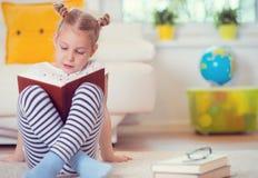 Porträt des klugen kleinen Mädchens, das mit Buch auf dem Boden sitzt Stockbilder