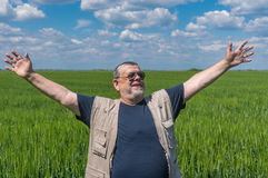 Porträt des lächelnden älteren Landwirts, der inneres unausgereiftes Erntefeld steht Stockfoto