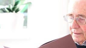 Porträt des lächelnden älterer Mann-Lesebuches zu Hause stock video footage