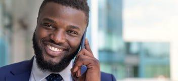 Porträt des lächelnden Afroamerikanergeschäftsmannes, der telefonisch draußen spricht Kopieren Sie Platz stockbild