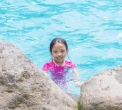 Porträt des lächelnden asiatischen Mädchen-Kindes an der Pool-Seite Stockfotografie