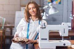 Porträt des lächelnden europäischen Modedesigners, der nahe bei der Nähmaschine hält ein Geschenk steht, verpackte im Kraftpapier Stockbild
