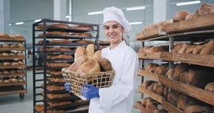 Porträt des lächelnden Frauenbäckers mit einem großen Korb der Weinlese mit einem frischen Brot, das gerade zur Kamera und haben  stock video
