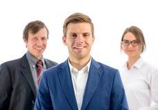 Porträt des lächelnden Geschäftsmann-Führers Looking an der Kamera auf Hintergrund von Geschäftsleuten Stockfoto